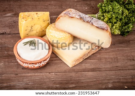 Various types of cheese on a wooden background with parsley.Tinted