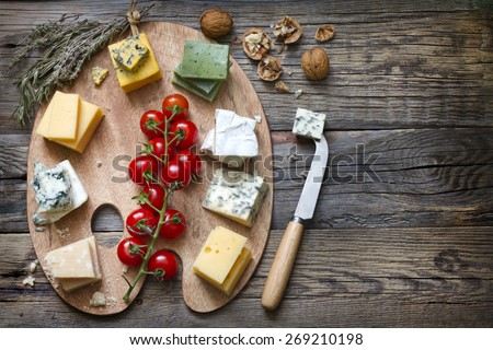 Various types of cheese on abstract vintage paint palette - stock photo