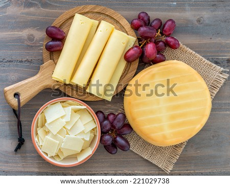 Various types of cheese on wooden background - stock photo