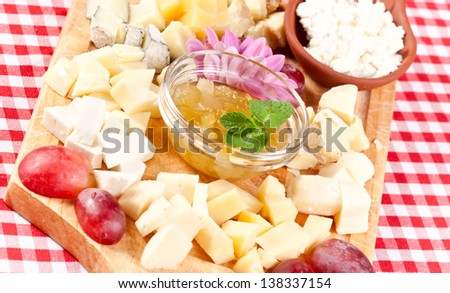 Various types of cheese on wooden platter - stock photo