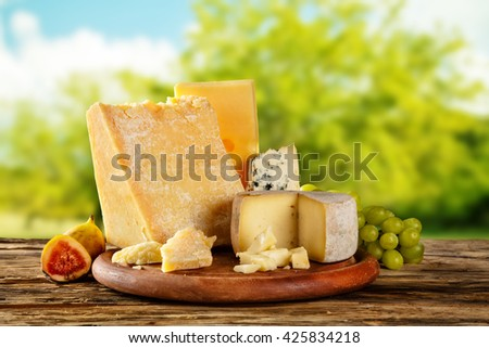 Various types of cheese placed on wooden table, copyspace for text with Blur abstract green background