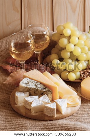 Various types of cheese served with grapes, walnuts, honey and white wine on sackcloth and wooden planks background