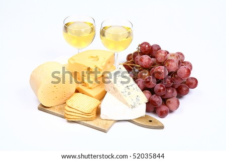 Various types of cheese (swiss, yellow, brie, blue cheese) with white wine, red grapes and crackers on white background
