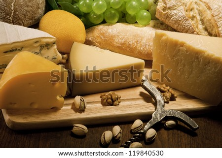 Various types of cheese with bread and fruit - stock photo