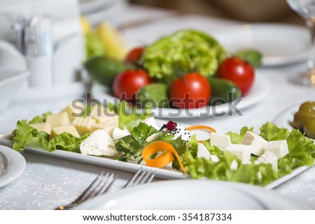 Various types of cheese with empty space background concept. Close up of a tray of assorted rustic bread and cheese with olives and grapes.  - stock photo