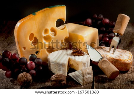 various types of cheese with grapes and nuts - stock photo