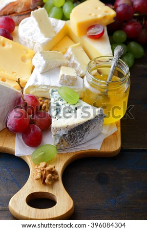 Various types of cheese with grapes, honey and walnuts on cutting board on old wooden table - stock photo