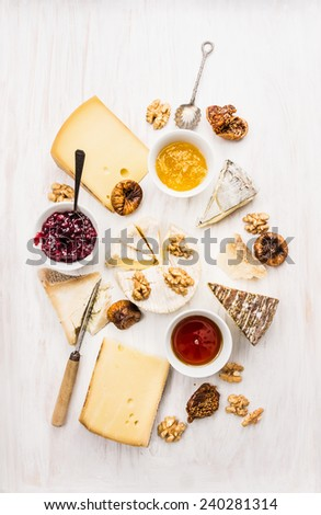 various types of cheese with sauce, walnut and figs on white wooden background - stock photo