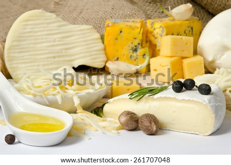Various types of cheese with spice on the wooden board - stock photo