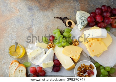 Various types of Cheeses with grapes, honey, bread and walnuts on the slate. Top view