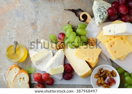 Various types of fresh Cheeses with grapes, honey, bread and walnuts on slate background. Top view