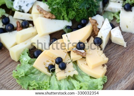 Various types of gourmet cheeses with green salad, wineberries and walnuts closeup on wooden platter background, horizontal picture - stock photo
