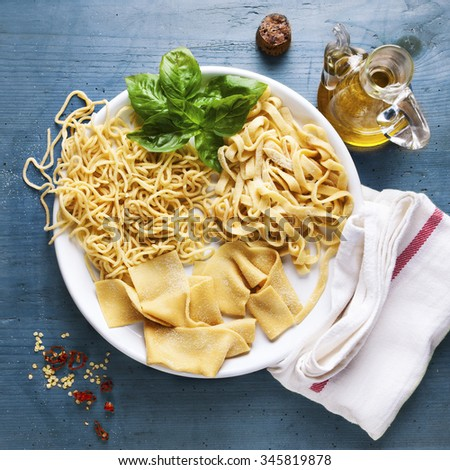 various types of Homemade Fresh Pasta on the plate on a Blue wooden background - stock photo