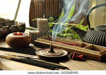 VARIOUS TYPES OF INCENSE WITH TEAPOT AND BUDDHA STATUE - stock photo