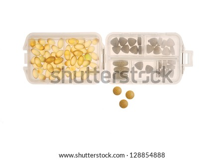 Various types of pills in a pillbox isolated on white - stock photo