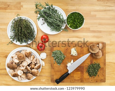 Various types of vegetables and chopping board with knife on kitchen counter - stock photo