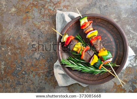 Various vegetables and meat kebabs on a dark plate, view from above - stock photo