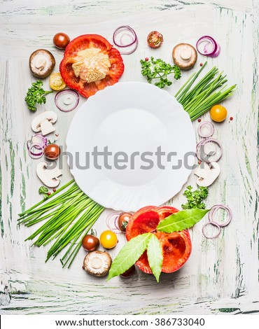 Various vegetables and seasoning cooking  ingredients around blank plate on light  rustic wooden background, top view composing. Healthy eating and diet food concept.  - stock photo