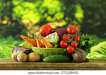 various vegetables (carrots, potatoes, cabbage, tomatoes) in basket on natural green background - stock photo