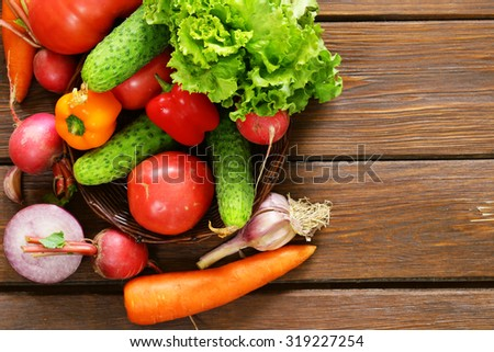 various vegetables for a salad (cucumbers, tomatoes, lettuce, radishes, carrots) on wooden background - stock photo