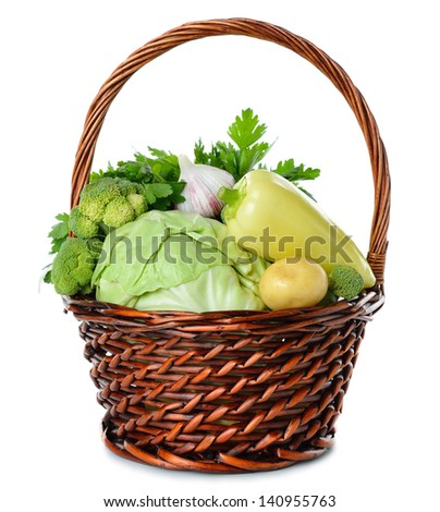 Various vegetables in a brown basket isolated on white background