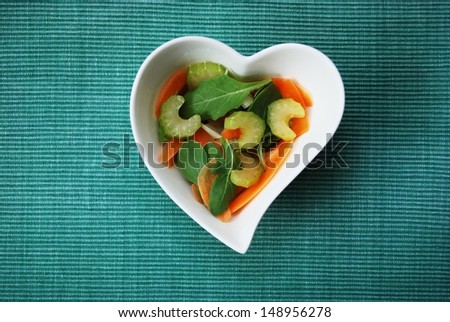 Various vegetables salad in heart shape bowl on green background, free space for text - stock photo