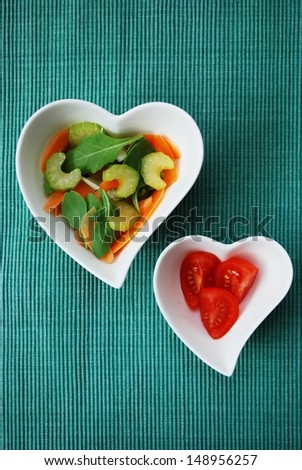 Various vegetables salad in two heart shape bowls on green background