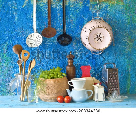 various vintage kitchen utensils,against blue wall  - stock photo