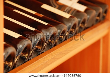 various wine bottles in row on wooden shelf