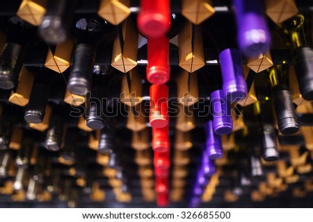 Various wine bottles in row on wooden shelf.  - stock photo