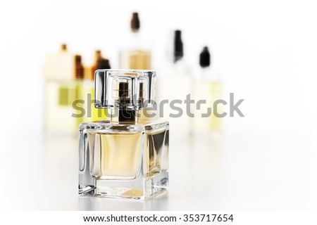 Various woman perfumes set on white background. Selective focus on front bottle, shallow DOF.