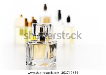 Various woman perfumes set on white background. Selective focus on front bottle, shallow DOF. - stock photo