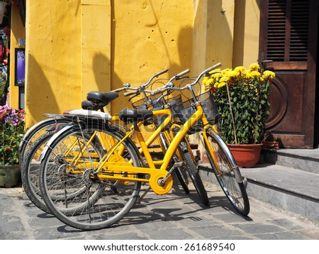 Various yellow bikes for rent in a row parked near yellow wall         - stock photo