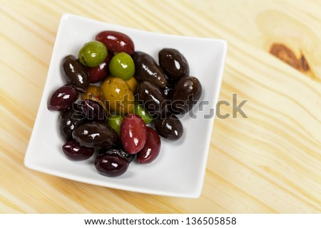 Varitey of olives in the bowl on wooden table