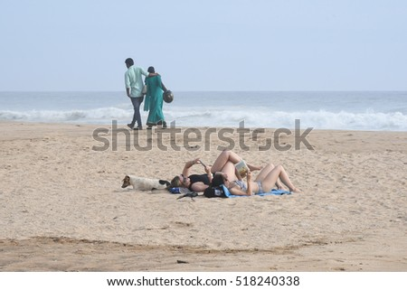 VARKALA, INDIA - SEPTEMBER 03: Couples walking by tourists sunbathing/relaxing with a street dog beside them on September 03, 2016 on Varkala beach/seashore, in Trivandrum, Kerala, India.