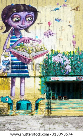 Varna, Bulgaria - August 30, 2015: Street art by unknown artist.  Wall school with a picture of a girl with a book and prehistoric animals