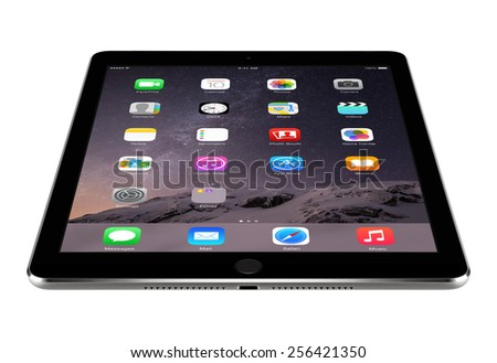 Varna, Bulgaria - February 04, 2014: Angled front view of Apple Space Gray iPad Air 2 displaying iOS 8 homescreen lies on the surface, designed by Apple. Isolated on white. The whole image in focus. - stock photo