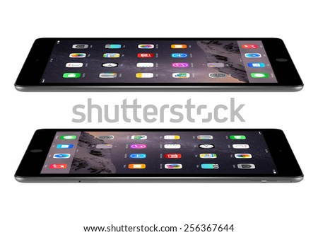 Varna, Bulgaria - February 03, 2014: Apple Space Gray iPad Air 2 with touch ID displaying iOS 8 homescreen lies on the surface, left and right side view, designed by Apple. The whole image in focus. - stock photo