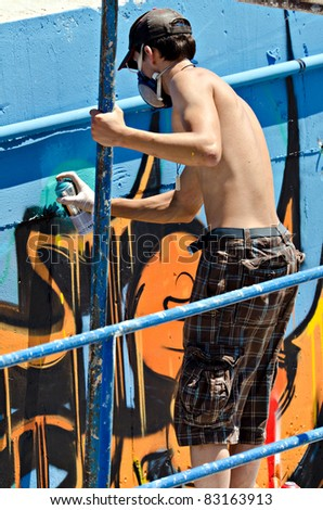 "VARNA, BULGARIA - JUNE 2: Graffiti artist on a scaffolding at the ""Creatures from Black Sea"" Sprite Graffiti Jam 2011 in Port of Varna, on June 2, 2011 in Varna, Bulgaria."