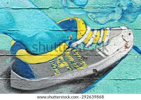 Varna, BULGARIA - June 21, 2015: Street art by unknown artist on a concrete wall close to Port of Varna of a sneaker with loose ties. - stock photo