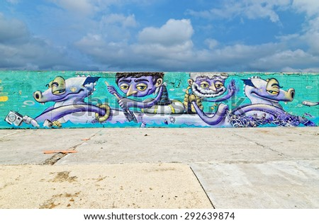 Varna, BULGARIA - June 21, 2015: Street art by unknown artist on a concrete wall close to Port of Varna of an abstract fishing boat with sailor holding an oar and an old man holding a fishing net. - stock photo
