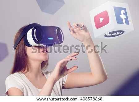 Varna, Bulgaria - March 10, 2016: Woman in VR headset looking up and interacting with Facebook Youtube Steam VR content. Facebook Google & Steam believes that VR is the future of content consumption. - stock photo