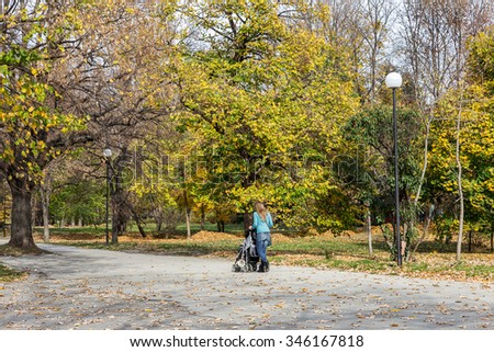 VARNA, BULGARIA - 13 November 2015: Autumn city park. Young mothers with small children walking in the park on a bright sunny day.