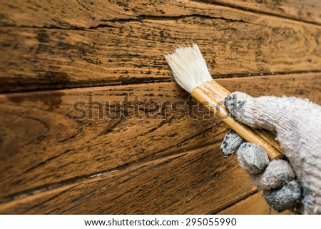 Varnish painting wooden surface with brush - stock photo