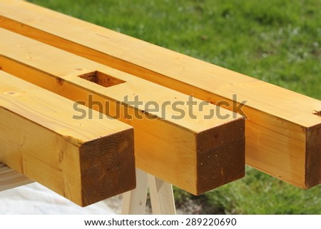Varnished timber posts with joints - stock photo