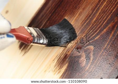 Varnishing a wooden shelf using paintbrush - stock photo