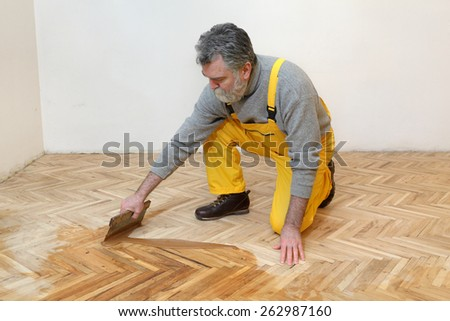 Varnishing of oak parquet floor, mature adult workers using tool