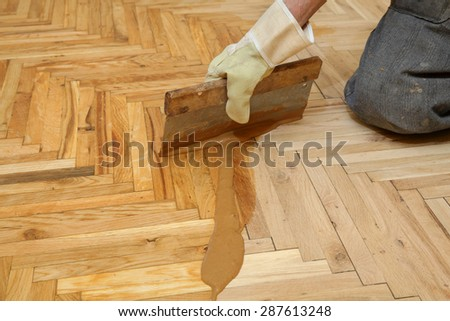 Varnishing of oak parquet floor, senior workers hand and tool - stock photo