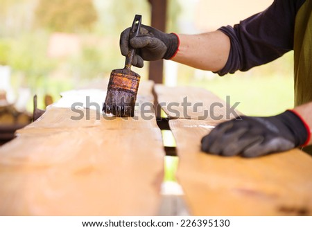 Varnishing of pine wooden planks, workers hand and paintbrush - stock photo