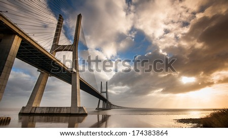 Vasco da Gama Bridge over the Tagus river at sunrise with cloudy sky. Lisbon, Portugal. It is the longest bridge in Europe (including viaducts), with a total length of 17.2 km (10.7 mi). - stock photo